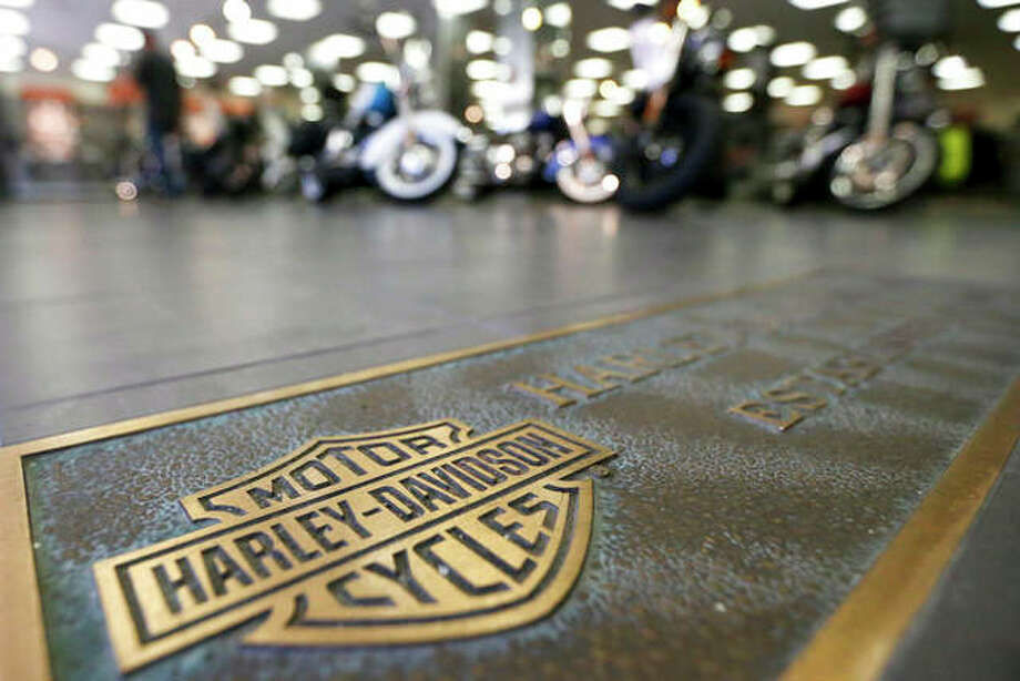 FILE - In this April 26, 2017, file photo, rows of motorcycles are behind a bronze plate with corporate information on the showroom floor at a Harley-Davidson dealership in Glenshaw, Pa. Harley-Davidson, facing rising costs from new tariffs, will begin shifting the production of motorcycles heading for Europe from the U.S. to factories overseas.