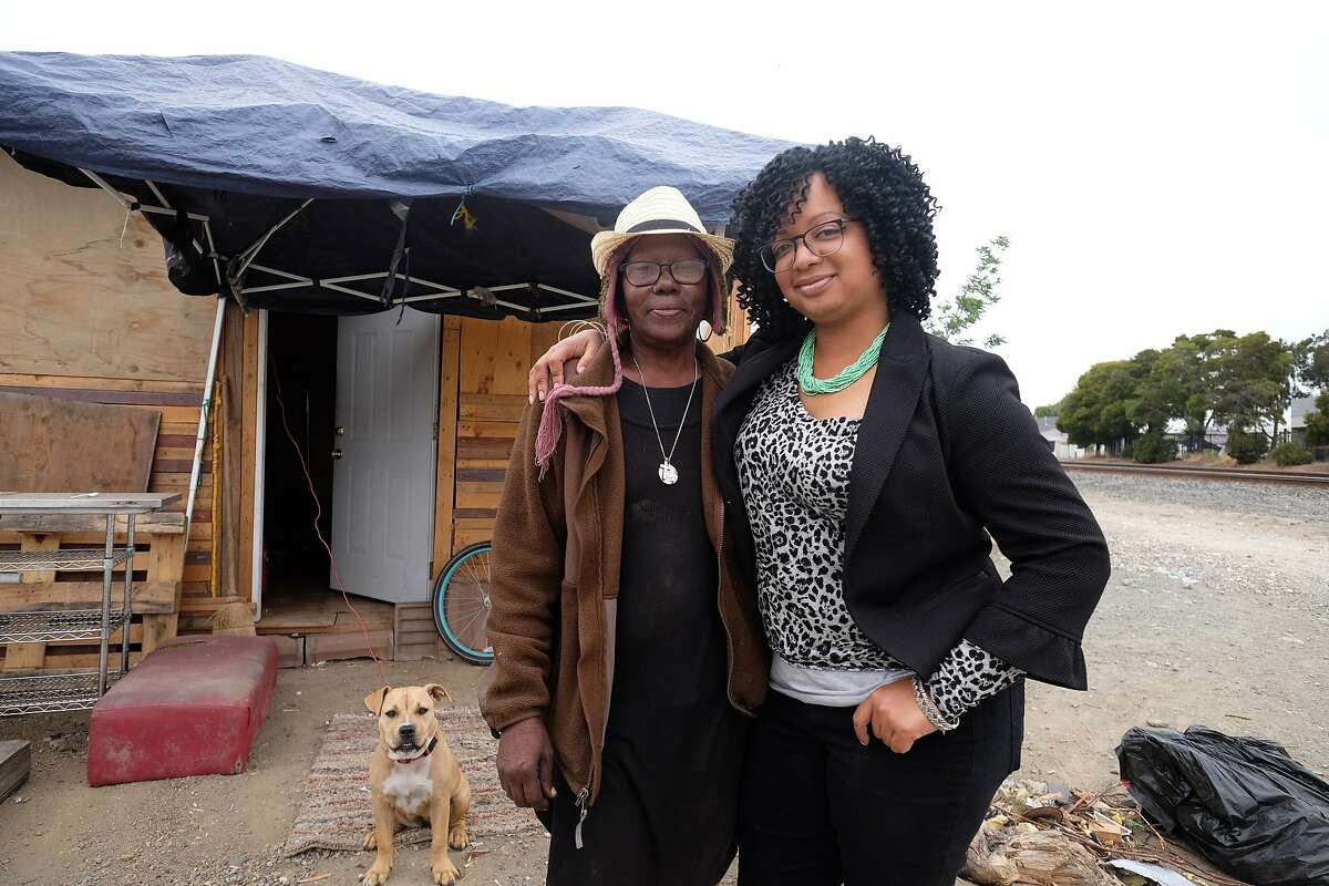 Candice Elder, 34, the founder of East Oakland Collective, stands with Elizabeth Easton, 65, in front of Easton's tiny home and her dog, Nala, at a homeless encampment in East Oakland on June 20, 2018.
