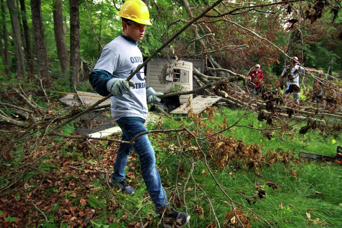 Justin Bizzotto carries storm debris in a yard at a house on Dutton Road in Oxford as members of the Oxford High School football team clean debris from the May 15 storm.