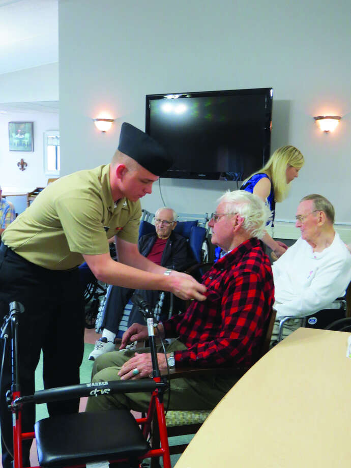 Navy ETN3 Brett Brown pins an American flag on a veteran during a ceremony at Eden Village.
