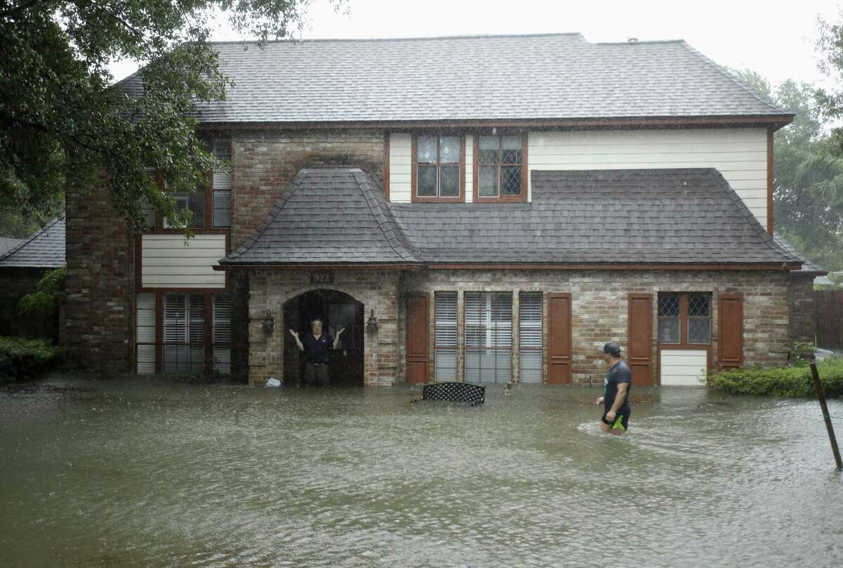 A man standing in the doorway of his flooded home responds to an evacuation offer in a neighborhood inundated by floodwaters from Hurricane Harvey in Houston on Aug. 28, 2017. FEMA will stop paying for hotel rooms for those still displaced by the hurricane on July 1.