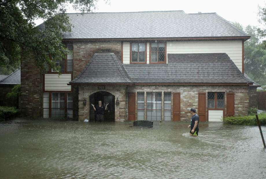 A man standing in the doorway of his flooded home responds to an evacuation offer in a neighborhood inundated by floodwaters from Hurricane Harvey in Houston on Aug. 28, 2017. FEMA will stop paying for hotel rooms for those still displaced by the hurricane on July 1. Photo: Charlie Riedel, STF / Associated Press / Copyright 2018 The Associated Press. All rights reserved.