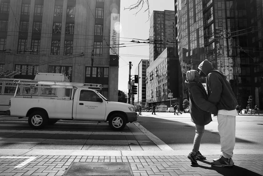 Shereese McIntosh (l to r) and Melvin Walker share a kiss as they stand on the corner of Market Street and Polk Street across from Twitter headquarters on their way to check out a SRO they might be moving to in the future  on Friday,  April 13,  2018, in  San Francisco, Calif.  McIntosh and Walker said they got help from the HOT team and Navigation Center before getting a spot in an n SRO a couple of weeks ago. Photo: Lea Suzuki / The Chronicle