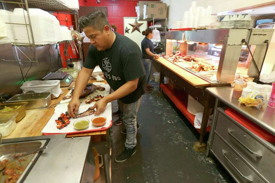 "Adrian Davila of Davila's BBQ prepares a meat plate in the Seguin restaurant his family operates. Davila will be featured Sunday in a Food Network show called ""BBQ Beat Down."" Photo: William Luther /Staff File Photo / © 2015 San Antonio Express-News"