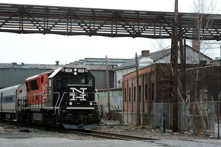 A Waterbury bound commuter train passes through the Ansonia Copper & Brass property in Ansonia, Conn. March 23, 2016.