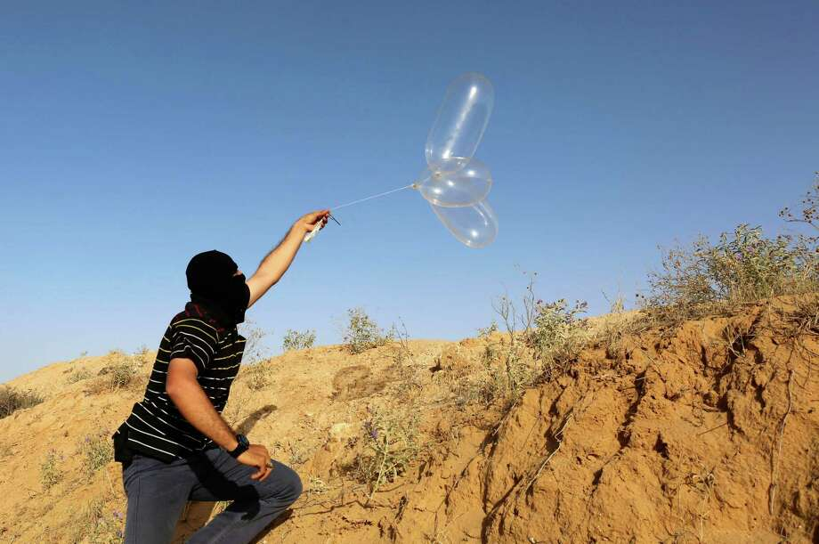 A masked Palestinian protester launches a Balloon loaded with flammable material to be flown toward Israel, at the Israel-Gaza border, in Rafah in the southern Gaza Strip on June 17, 2018.  / AFP PHOTO / SAID KHATIBSAID KHATIB/AFP/Getty Images Photo: SAID KHATIB / AFP/Getty Images / AFP or licensors