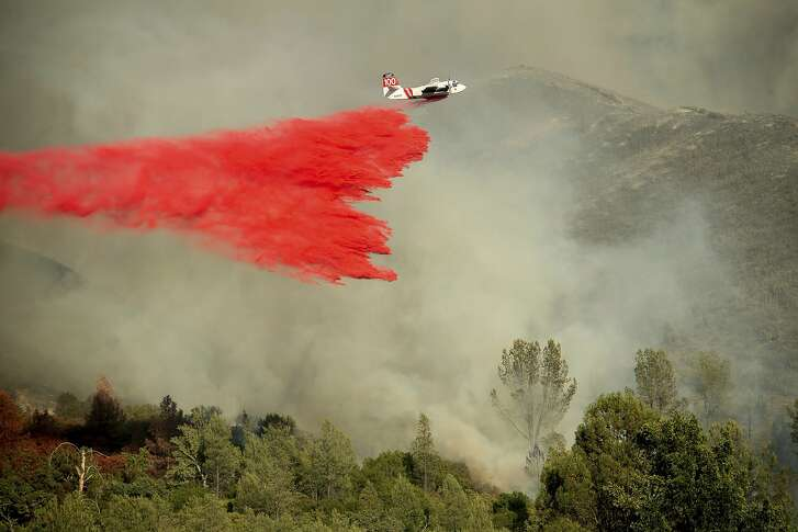 An air tanker drops retardant on a wildfire burning above the Spring Lakes community on Sunday, June 24, 2018, near Clearlake Oaks, Calif. Wind-driven wildfires destroyed buildings and threatened hundreds of others Sunday as they raced across dry brush in rural Northern California. (AP Photo/Noah Berger)