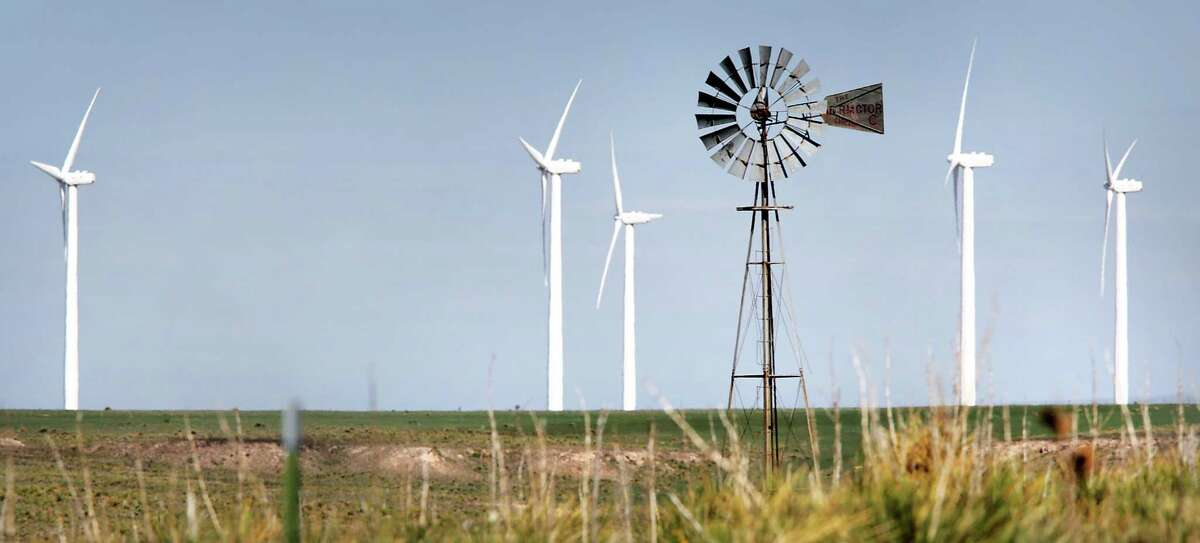 An old windmill that pumps water for cattle is framed by the new wind turbines that produce electricity along Highway 287 just north of Amarillo in 2013.