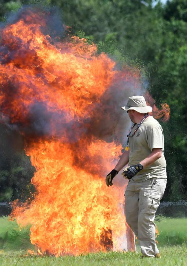 An agent from the Bureau of Alcohol, Tobacco and Firearms throws a Molotov cocktails at the Beaumont Police Department training grounds on Monday. Held every few years, the event served as training to teach area first responding about explosive devices. The Bureau denoted about a dozen different devices to show a sampling of types of explosions.  Photo taken Monday, 6/25/18 Photo: Guiseppe Barranco/The Enterprise