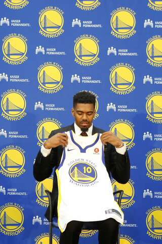 35c781d3952 Golden State Warriors NBA basketball draft pick Jacob Evans holds his new  jersey at a press