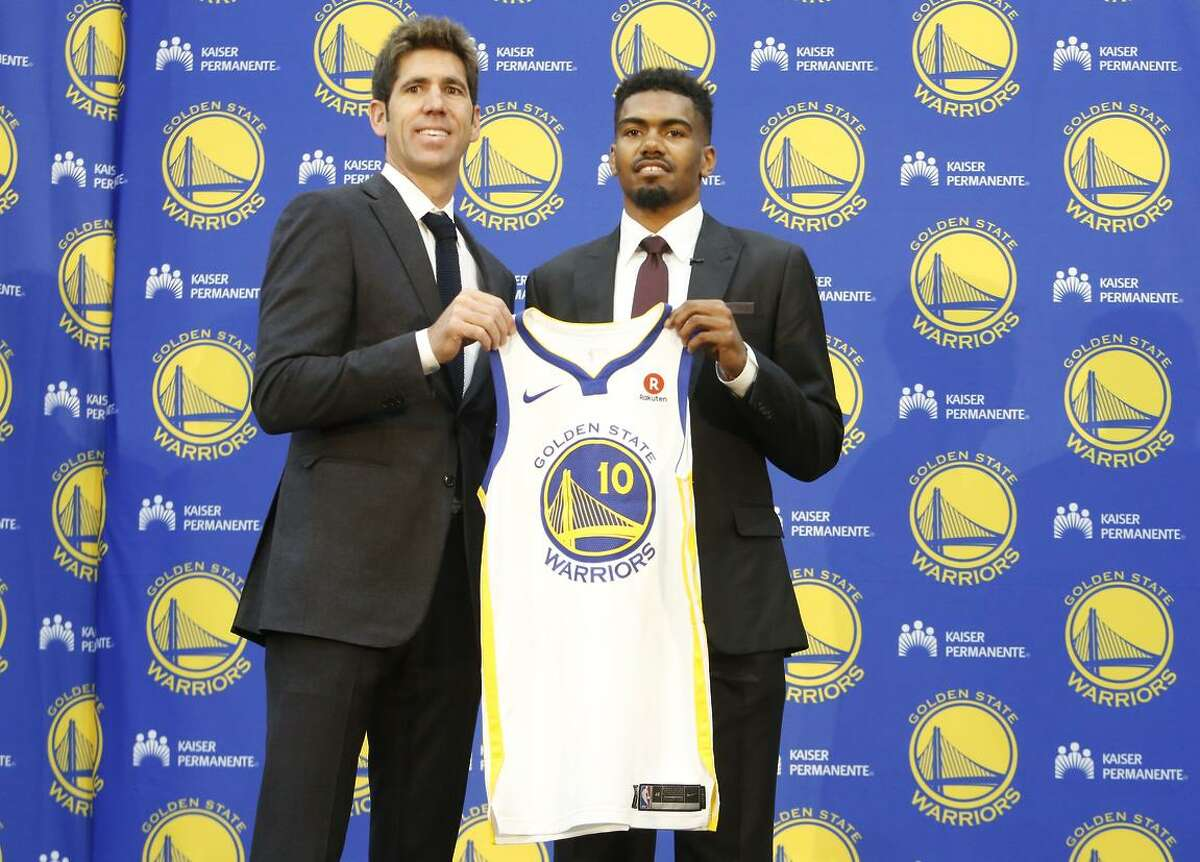 Warriors president of basketball operations Bob Myers poses with Golden State Warriors NBA basketball draft pick Jacob Evans as he holds up his new jersey at a news conference at the Rakuten Performance Center on Monday, June 25, 2018 in Oakland, Calif.