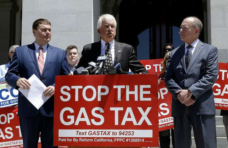 Republican gubernatorial candidate John Cox, center, blasts a recent gas tax increase during a news conference Monday, June 18, 2018, in Sacramento, Calif. Cox is the chairman of a campaign to repeal the gas tax increase and faces Democratic Lt. Gov. Gavin Newsom in November. Cox is flanked by Carl DeMaio, left, chairman of Reform California, and Jon Coupal, right, president of the Howard Jarvis Taxpayers Association. (AP Photo/Rich Pedroncelli)