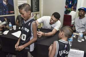 Danny Green autographs a uniform in 2016 of Laredoan Nathan Ramos during an autograph session at Samson in downtown Laredo.