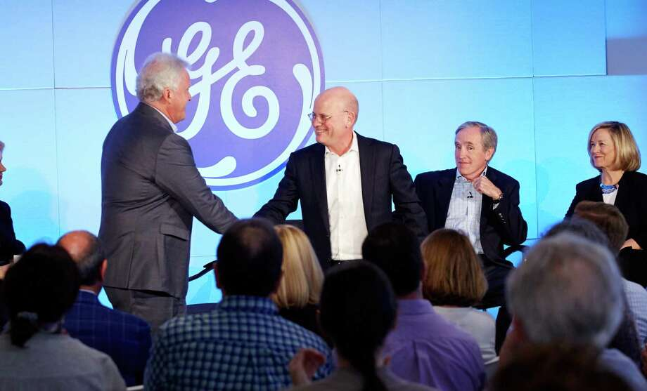 John Flannery (center right) extends a smile and handshake with Jeff Immelt, after GE's June 2017 announcement that Flannery would succeed Immelt as GE CEO effective in August that year. (File photo by Joel Benjamin courtesy General Electric) / Joel Benjamin