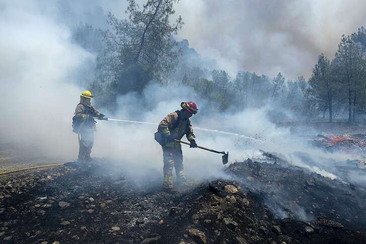 Fire crews battle a wildfire near Cache Creek Road in Spring Valley, Calif., Monday, June 25, 2018. Thousands were forced to flee their homes Monday as major wildfires encroached on a charred area of Northern California still recovering from severe blazes in recent years, sparking concern the state may be in for another destructive series of wildfires this summer. (Paul Kitagaki Jr./The Sacramento Bee via AP)