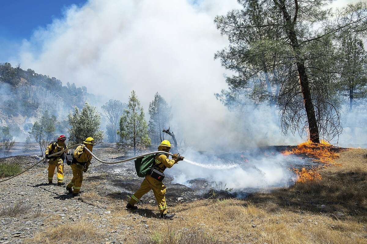 Fire crews battle a wildfire near Cache Creek Road in Spring Valley, Calif., Monday, June 25, 2018. Thousands were forced to flee their homes Monday as major wildfires encroached on a charred area of Northern California still recovering from severe blazes in recent years, sparking concern the state may be in for another destructive series of wildfires this summer.