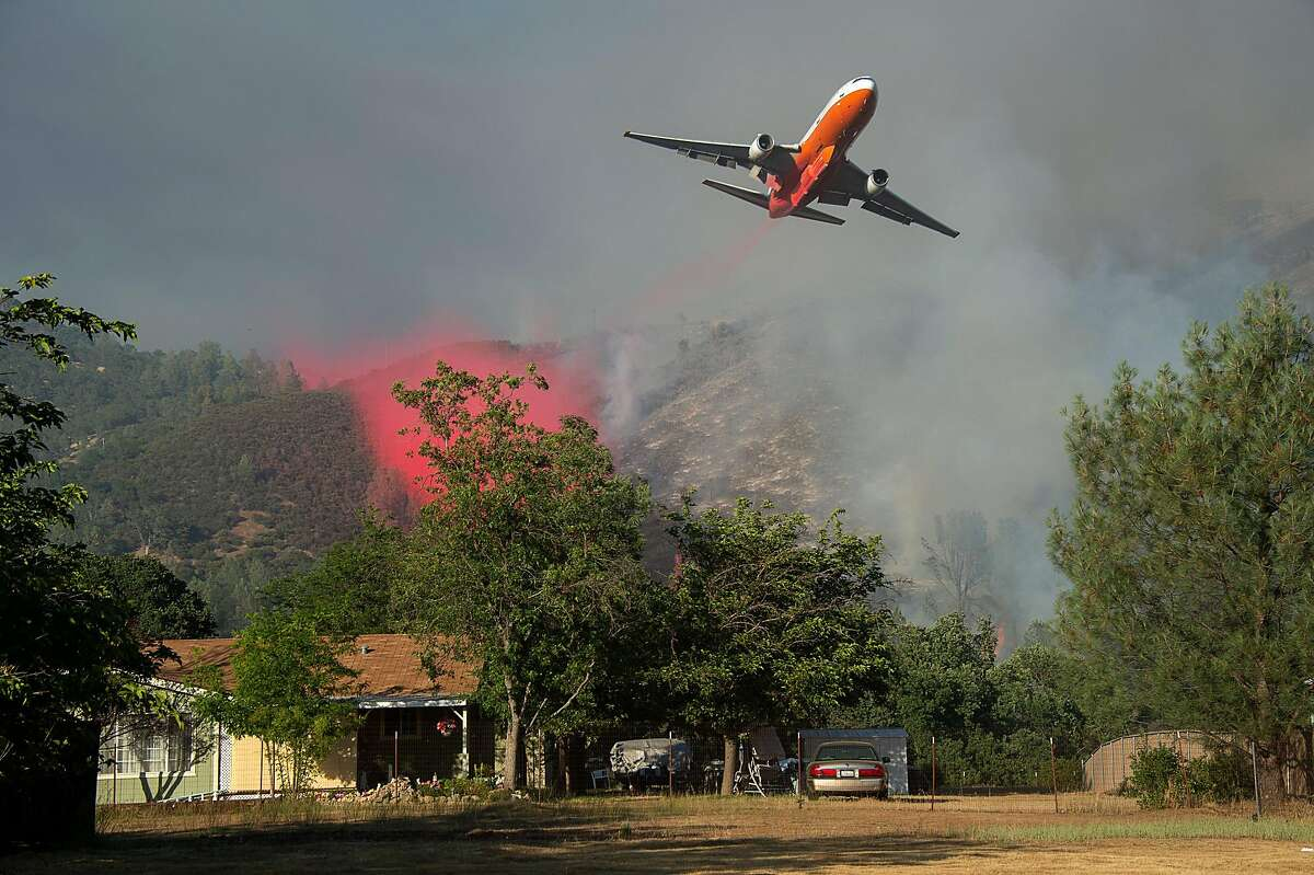 A Cal Fire jet dumps fire retardant as they battle the Pawnee fire in on Sunday, June 24, 2018 in Spring Valley.