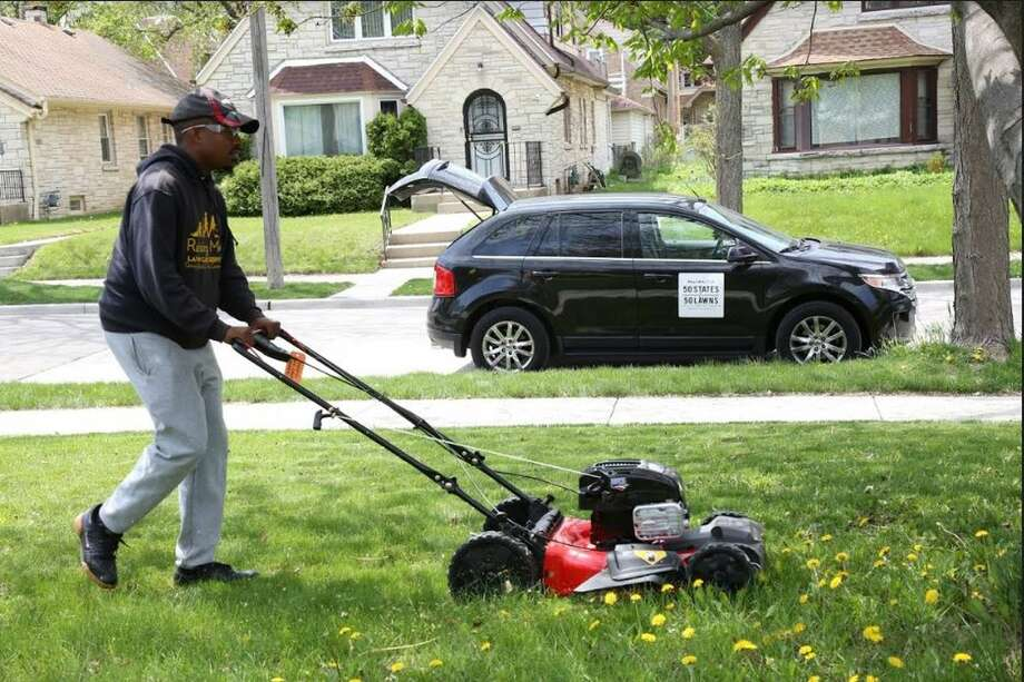 Rodney Smith, 28, of Alabama mows a lawn in Milwaukee. He's mowing lawns across the country for free to help people in need. Photo: Courtesy Of Rodney Smity.