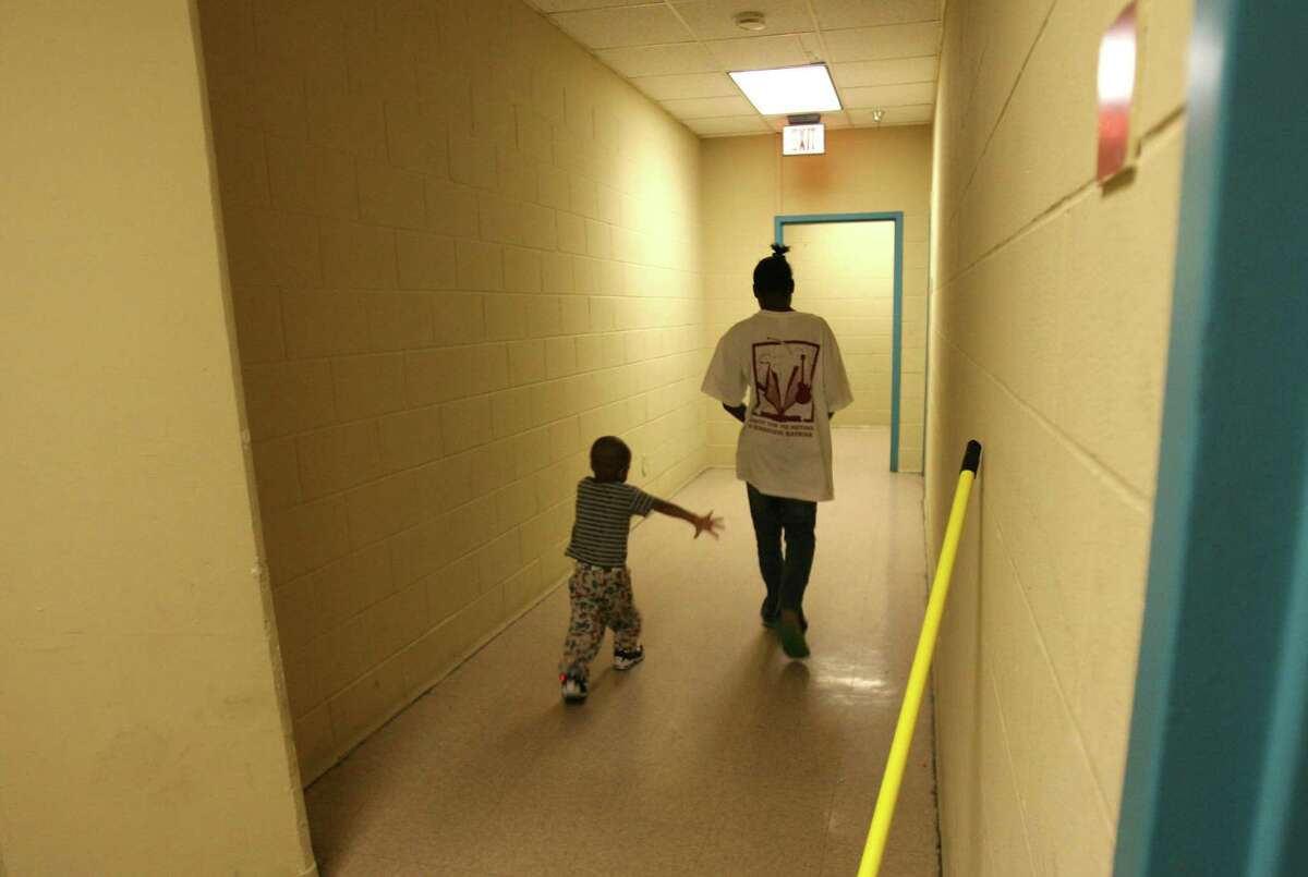 WELL-BEING TEXAS RANK: 35, with more than 1.6 million Texas children living in poverty, according to the 2018 Kids Count Data Book. Above: Myron Powell, 2, and his cousin Deiondrea, 13, walk in the corridor of the family dorm at the Salvation Army homeless shelter in Austin in 2006.