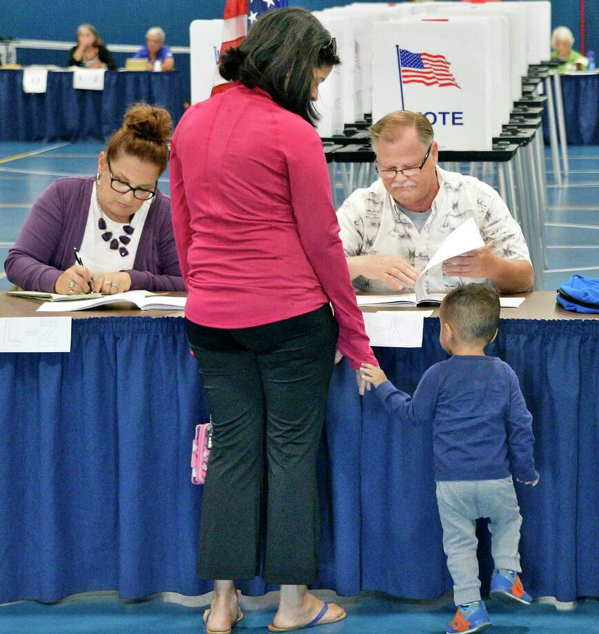 Ana Corona-Hall and son Matthew, 2, sign in with election inspectors Donna and Chris Gundersen to vote in the 21st Congressional District primary at the Gavin Park gym Tuesday June 26, 2018 in Wilton, NY.  (John Carl D'Annibale/Times Union) Photo: John Carl D'Annibale, Albany Times Union