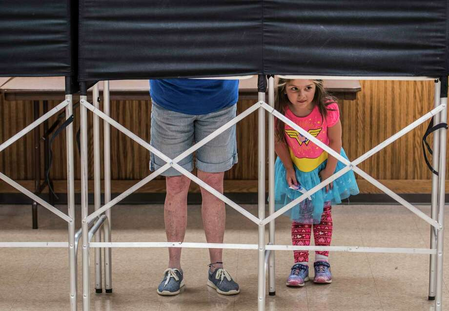 Chloe Day, 4 peers out from under the voting booths as her grandmother Nancy Marchione casts her ballot during the Democratic primary for the 19th Congressional District at the Brunswick #1 Fire Company firehouse Tuesday June 26, 2018 in Brunswick, N.Y. (Skip Dickstein/Times Union) Photo: SKIP DICKSTEIN, Albany Times Union
