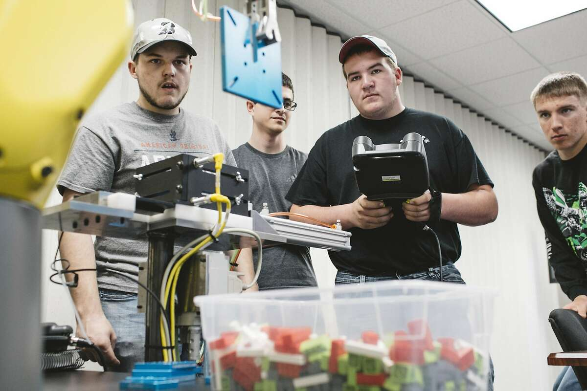 Austin Henderson, left, a high school student, learns how to program robots at APT Manufacturing Solutions in Hicksville, Ohio, May 10, 2018. The pool of skilled workers is shallow in the area near the Ohio-Indiana border where APT is based. The company has responded in part by teaching manufacturing skills to high school students. (Andrew Spear/The New York Times)