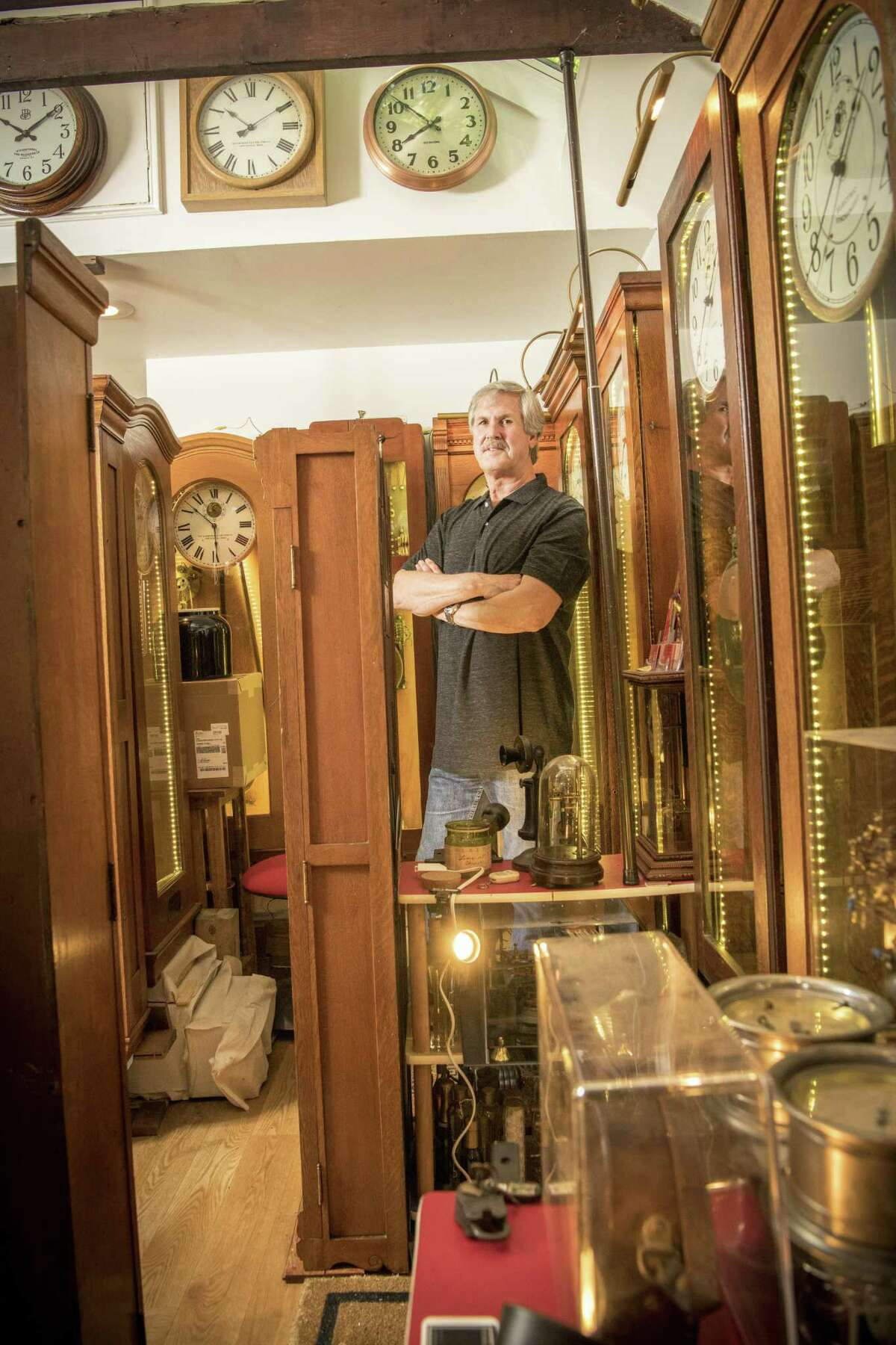 Dave Deitrich with some of his restore clocks in his tiny Stamford workshop.