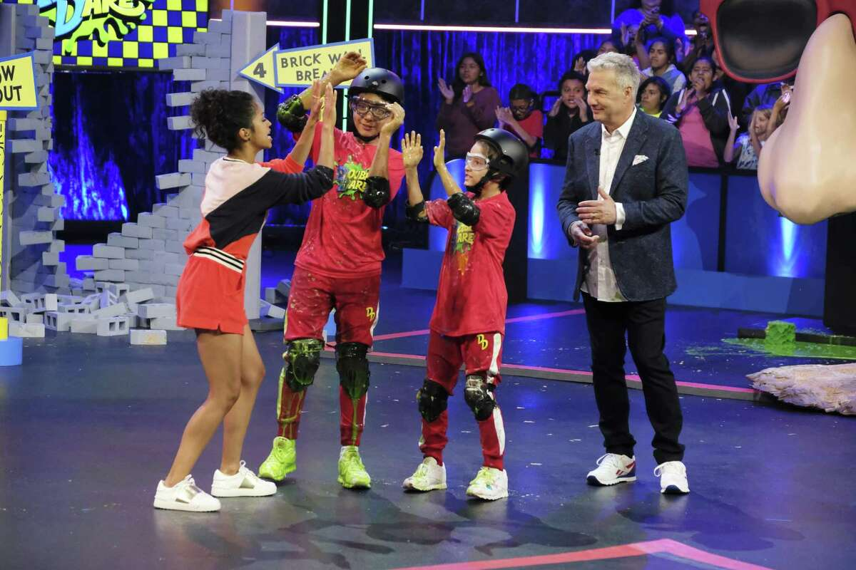 Liza Koshy (left) and Marc Summers (right) with contestants on the reboot of the game show