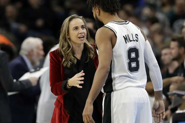 FILE - In this Dec. 26, 2017, file photo, San Antonio Spurs assistant coach Becky Hammon, left, talks with guard Patty Mills (8) during the second half of an NBA basketball game against the New York Nets, in San Antonio. A diversity report released shows the NBA continues to lead the way in men's professional sports in racial and gender hiring practices. The league earned an A+ for racial hiring practices and a B for gender hiring practices for an overall grade of an A. (AP Photo/Eric Gay, File)