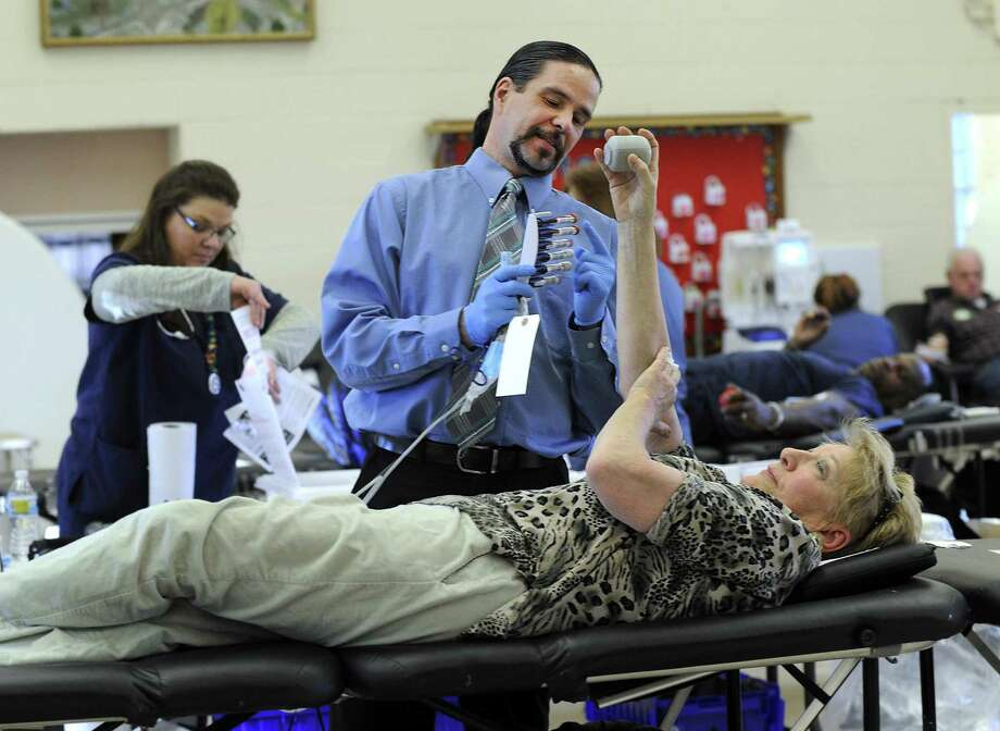Pat Pattonelli with the American Red Cross, works with Barbara Roper of New Fairfield who is donating blood at a blood drive at the New Fairfield Congregational Church Monday, February 29, 2016. Roper gives blood regularly, donating about 80 pints over the years. The American Red Cross does five of these drives in New Fairfield a year, split between the Congregational Church and St. Edward the Confessor locations. Photo: Carol Kaliff / Hearst Connecticut Media / The News-Times