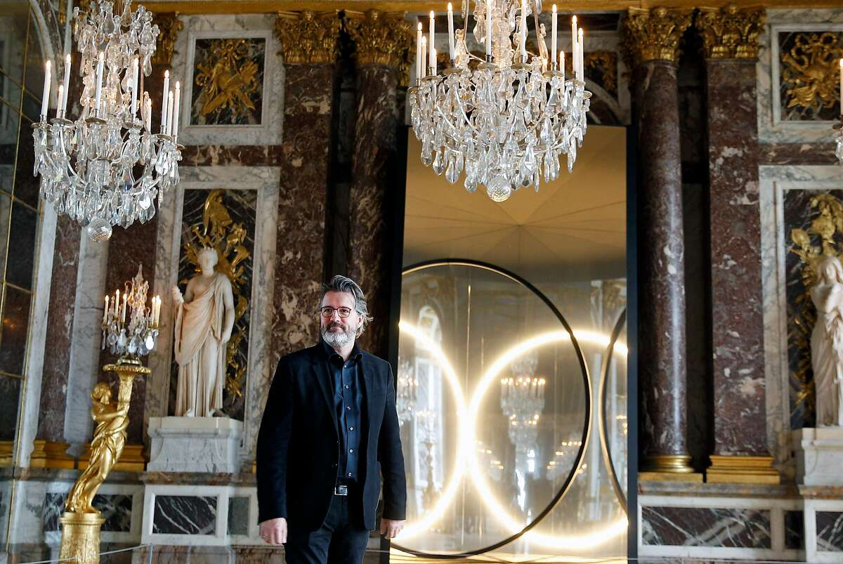 """VERSAILLES, FRANCE - JUNE 06: Danish-Icelandic artist Olafur Eliasson poses in front of his artwork named """"Your sense of unity"""" at the opening of the exhibition of his works in the hall of mirrors of the Chateau de Versailles on June 6, 2016, in Versailles, France. This exhibition takes place from June 7 until October 01, 2016. (Photo by Chesnot/Getty Images)"""