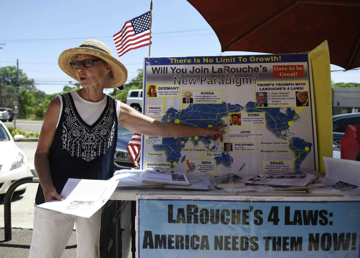 """Judy Clark distributes information at the LaRouche PAC stand set up near the U.S. Post Office in the Cos Cob section of Greenwich, Conn. Tuesday, June 26, 2018. The political action committee, named after Lyndon LaRouche, asks to end the """"coup"""" against President Trump, support China's One Belt One Road Initiative, and support LaRouche's economic policies reinstating the Glass?-Steagall banking separation act and returning to a national banking system."""