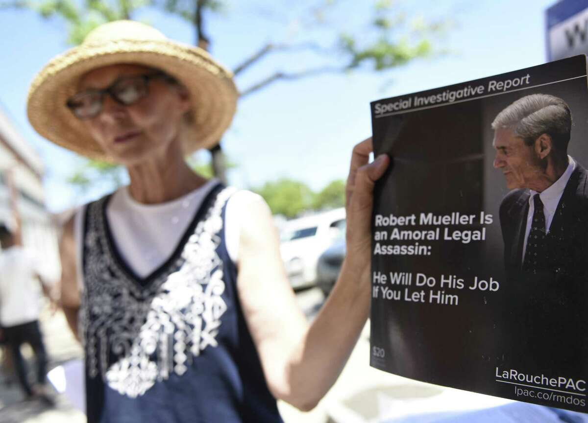 Judy Clark distributes information at the LaRouche PAC stand set up near the U.S. Post Office in the Cos Cob section of Greenwich, Conn. Tuesday, June 26, 2018. The political action committee, named after Lyndon LaRouche, asks to end the