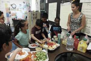 "McQueeney Elementary School second-grade math teacher Savanna Bartolo (right) serves a meal to her students before an after school class with parents and students on Thursday, May 10, 2018. Bartolo was showing the parents and their children a math-based game that they could play over the summer in hopes that the game would retain their math skills. Houston-based non-profit Children at Risk's 2018 school rankings, which highlight high-performing high-poverty schools, show that San Antonio is not closing the gap with the other big cities in Texas and SAISD in particular is not moving the needle fast enough. McQueeney did well on this year's rankings and was named a ""gold ribbon"" elementary school. (Kin Man Hui/San Antonio Express-News)"
