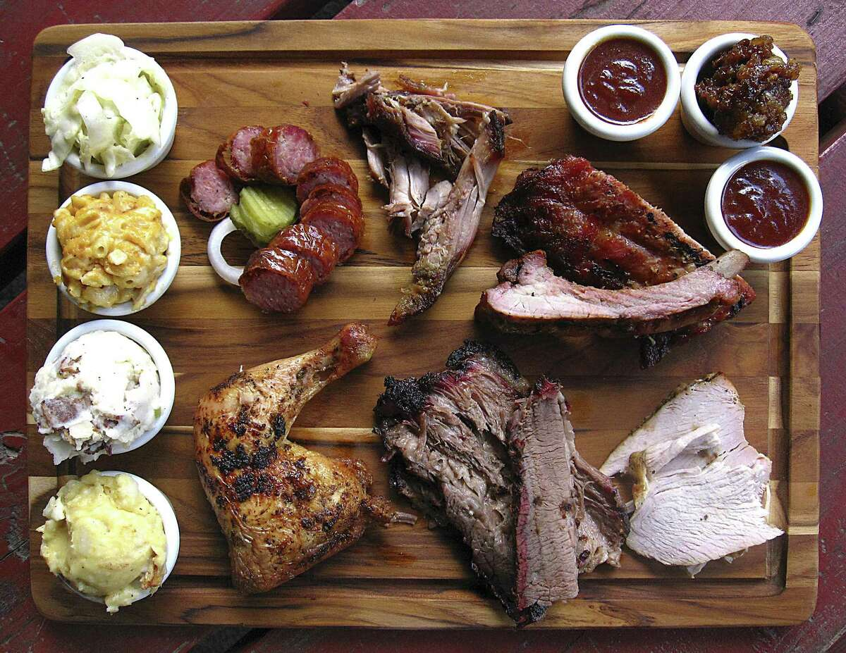 Meat and sides from Texas Pride Barbecue. Clockwise from bottom left: cheesy mashed potatoes, German potato salad, mac and cheese, cole slaw, sausage, pulled pork, baby back pork ribs, regular barbecue sauce, pecan cobbler, spicy barbecue sauce, turkey breast, brisket and chicken.