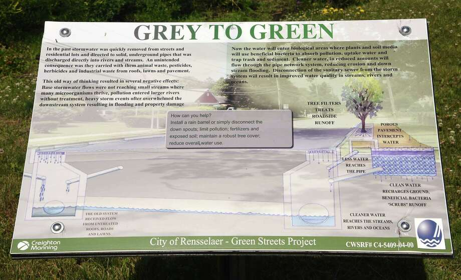 A grey to green sign is seen at a rain garden near a small housing subdivision on Washington Avenue on Tuesday, June 26, 2018 in Renssealer, N.Y. The rain garden is meant to catch and hold rainwater, so it does not flow directly into the sewers. (Lori Van Buren/Times Union) Photo: Lori Van Buren / 20044207A