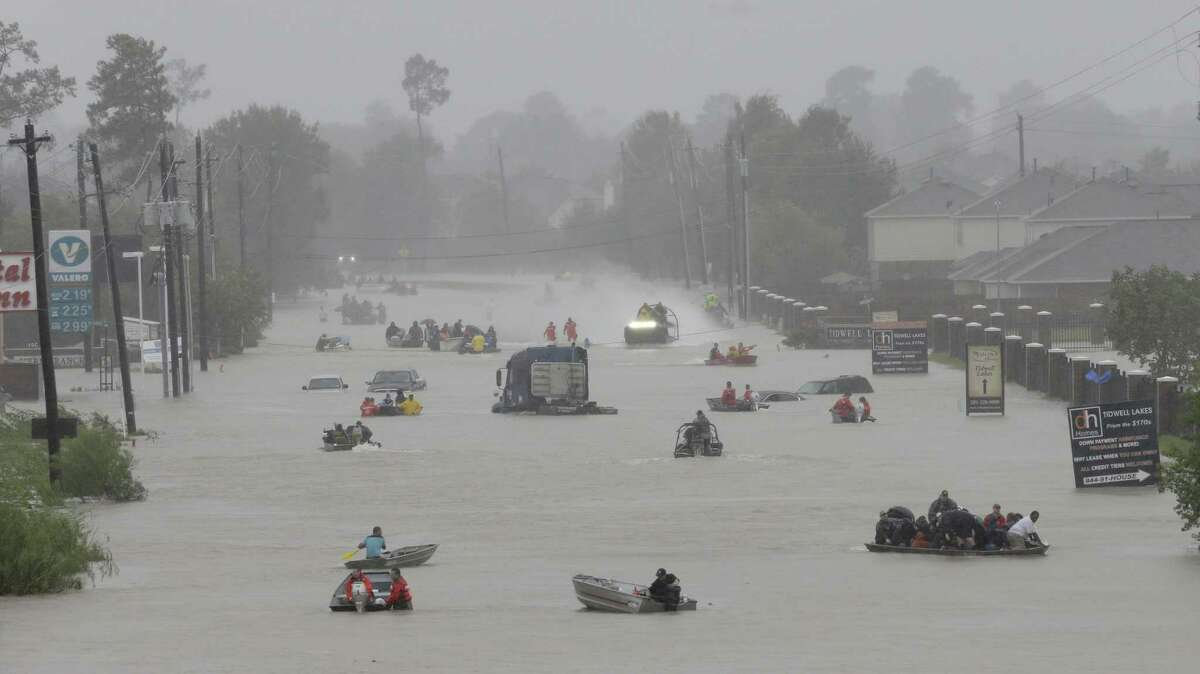 Rescue boats of every shape, manner, and size make their way along Tidwell near the east Sam Houston Tollway. Moving people to safety included first responder and volunteer efforts. ( Melissa Phillip / Houston Chronicle )