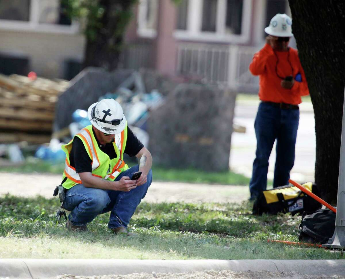 A construction worker checks his phone near Coryell Memorial Healthcare System hospital where an explosion in a building under construction injured several people, and knocked power out for a large portion of the city, Tuesday, June 26, 2018, in Gatesville, Texas. (Rod Aydelotte/Waco Tribune-Herald via AP)