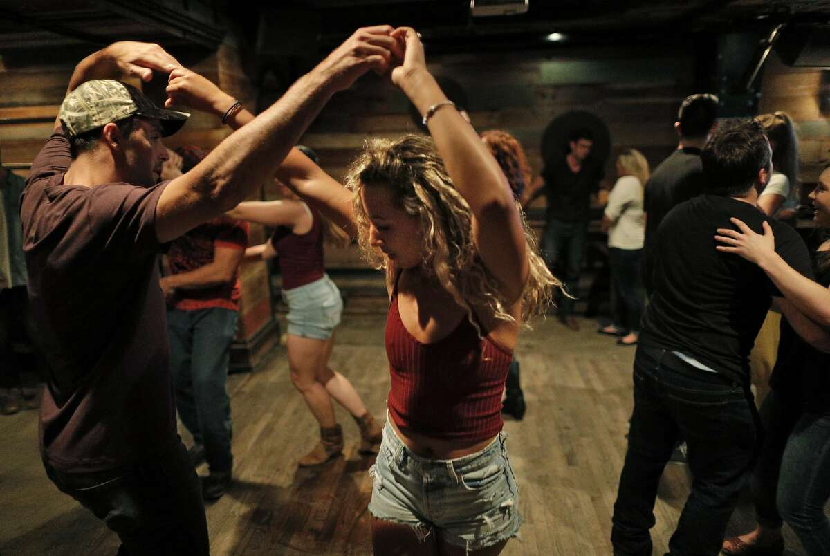 Genay Vaughn and Paolo Mancasola dance during weekly line dancing lessons at Jaxson, a bar in the Marina that specializes in country music, in San Francisco, Calif., on Sunday, June 24, 2018.