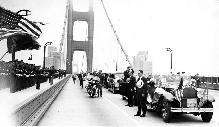 President Franklin D. Roosevelt visits the San Francisco Bay Area, July 14, 1938, seen here taking off his hat for the Natoinal  Anthem, during his crossing the Golden Gate Bridge