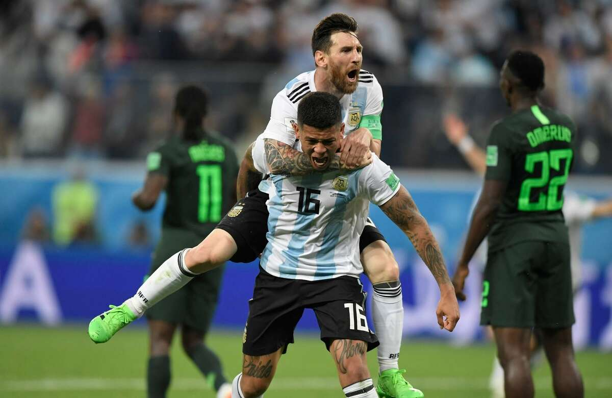 Argentina's Marcos Rojo (16) and Lionel Messi react after Rojo's late goal beat Nigeria and put Argentina in a quarterfinal.