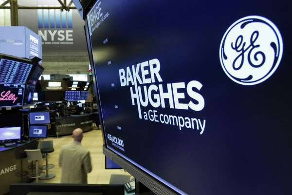 The logo for Baker Hughes appears above a trading post on the floor of the New York Stock Exchange, Tuesday, June 26, 2018. General Electric shed more of its major assets, announcing plans to cast away its health care business and sell its interests in the oil-services company, Baker Hughes. (AP Photo/Richard Drew)