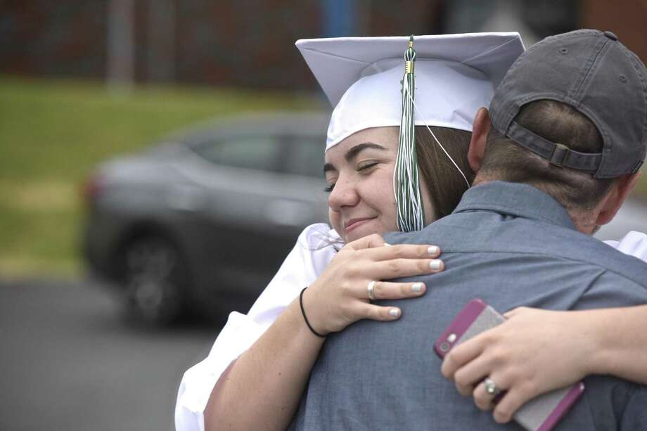 Rebecca Anne McGee gets a hug from her dad, Michael McGee, before the start of the New Milford High School 2018 Graduation, Saturday June 23, 2018, at The O'Neil Center, Western Connecticut State University, Danbury, Conn. Photo: H John Voorhees III / Hearst Connecticut Media / The News-Times