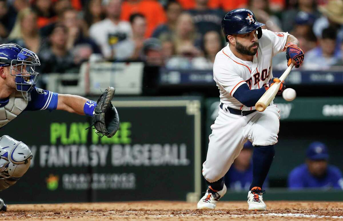 Houston Astros second baseman Jose Altuve (27) hits a sacrifice bunt in front of Toronto Blue Jays catcher Luke Maile, moving Alex Bregman to third, during the seventh inning of a major league baseball game at Minute Maid Park on Tuesday, June 26, 2018, in Houston.