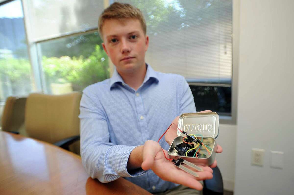 Ryan Edkins, a rising senior at AITE, holds a prototype for Moist-True, a moisture detection system that links to your phone and tells you how much water to put in houseplants, inside the Advocate office on Washington Boulevard in downtown Stamford on Monday.