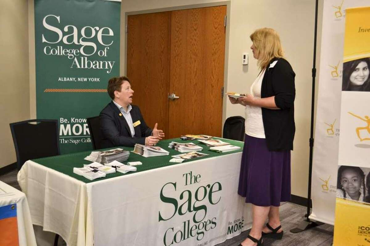 People talking in front of a table for the Sage Colleges during the 2017 Working to Make a Difference nonprofit exposition. (File photo)