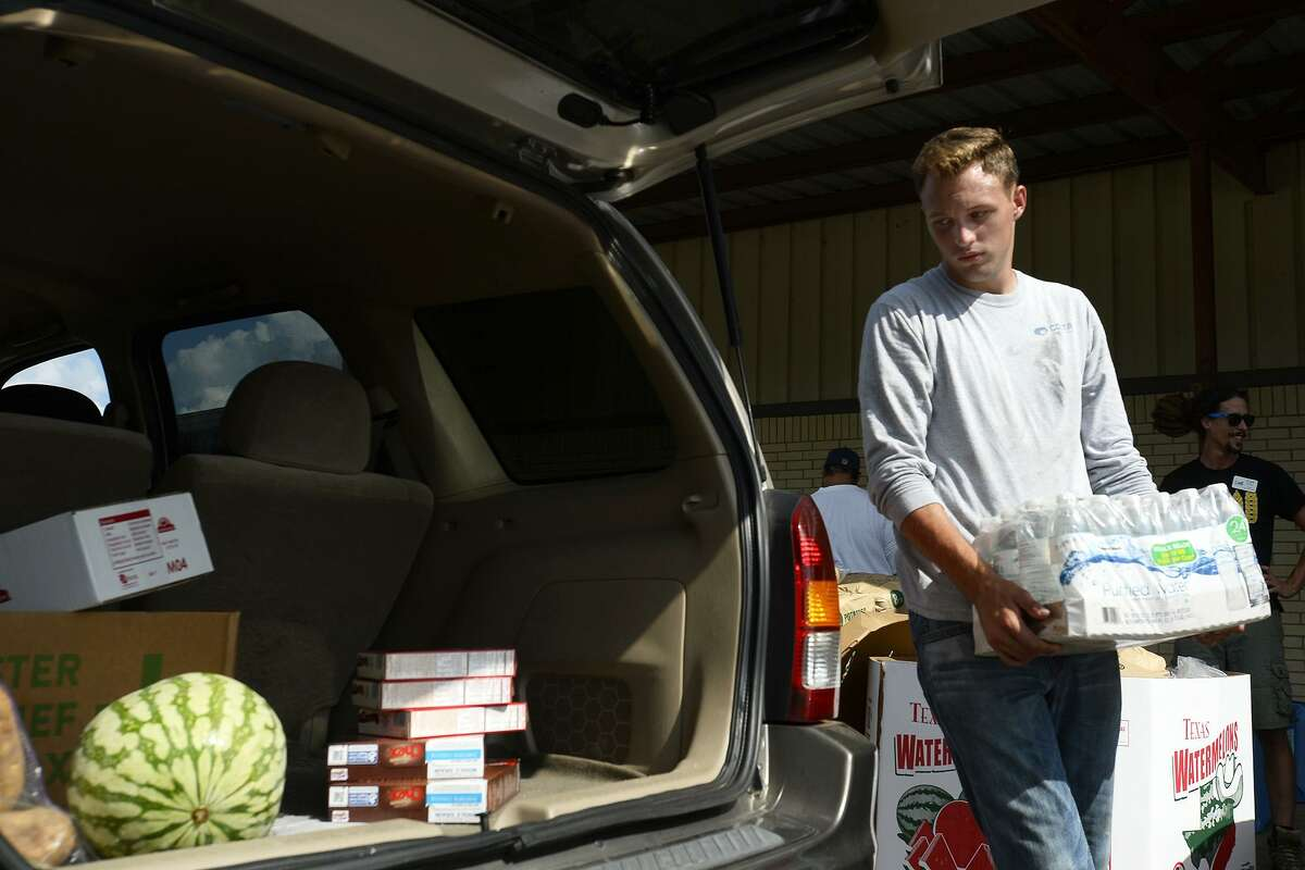 William Sumner helps load bottled water into a car at Hardin County Strong and the Southeast Texas Food Bank's disaster relief food distribution in Silsbee. The organization will hold another on Thursday at the former courthouse annex in Kountze.