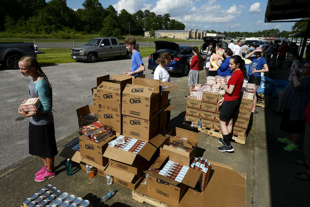 Volunteers help load food at Hardin County Strong and the Southeast Texas Food Bank's disaster relief food distribution in Silsbee. The organization will hold another on Thursday at the former courthouse annex in Kountze.