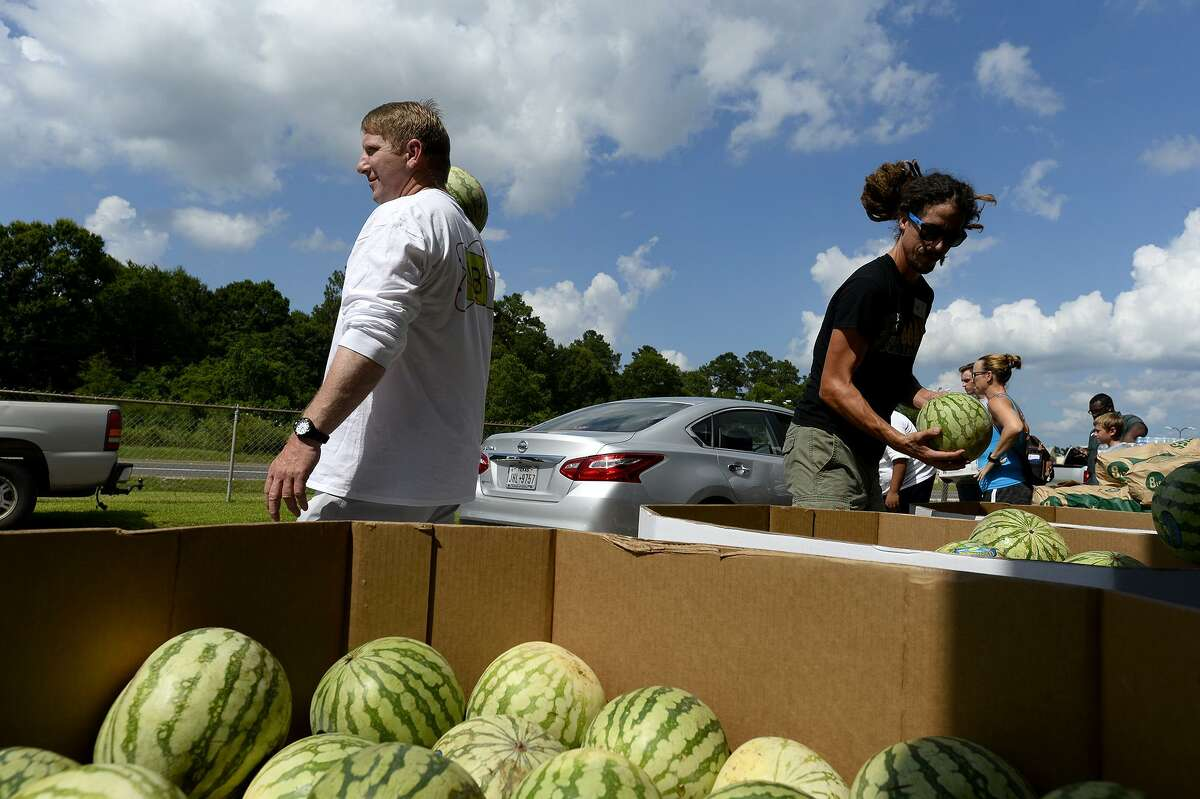 Alan McKinney, left, helps hand out watermelons at Hardin County Strong and the Southeast Texas Food Bank's disaster relief food distribution in Silsbee. The organization will hold another on Thursday at the former courthouse annex in Kountze. Photo taken Tuesday 6/26/18 Ryan Pelham/The Enterprise