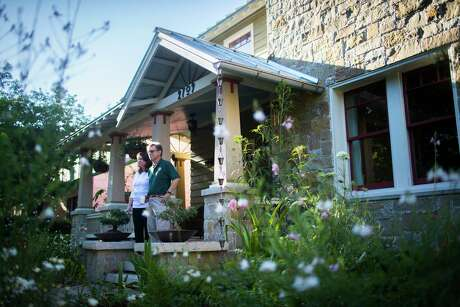 Kathleen English and her husband Steven Stelzer on their front porch, which overlooks an eclectic cottage garden designed to retain and reuse rainwater.